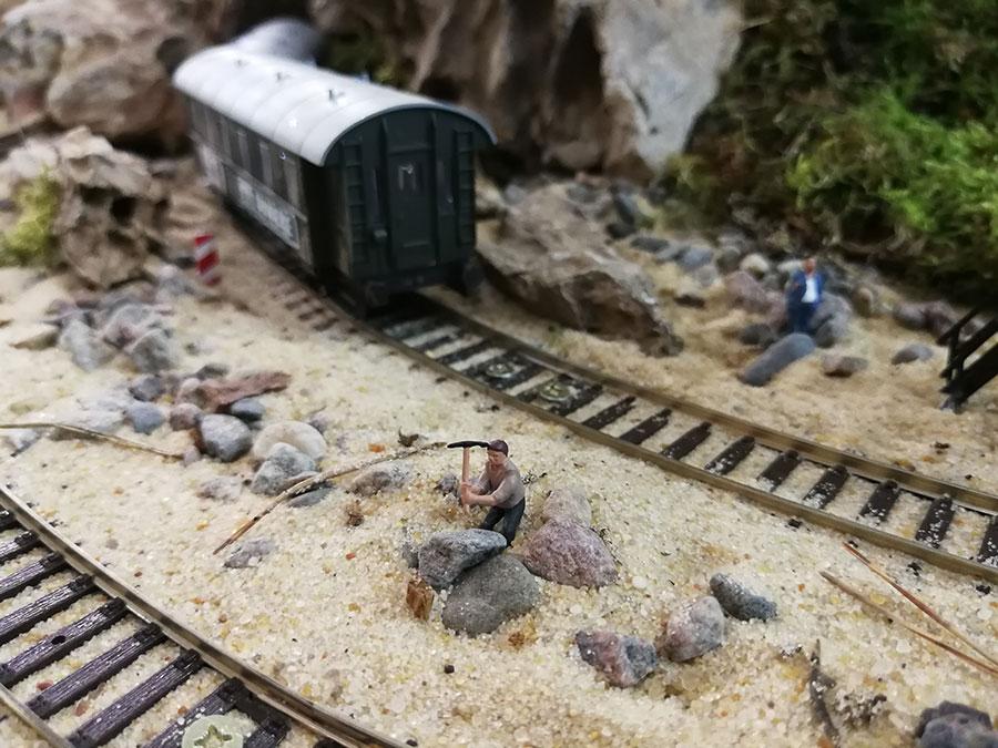 паровоз,человек,песок,камни