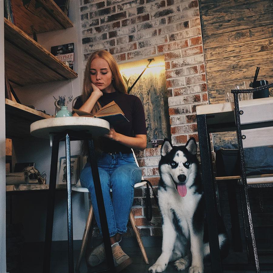 девушка с книгой и собакой в кафе