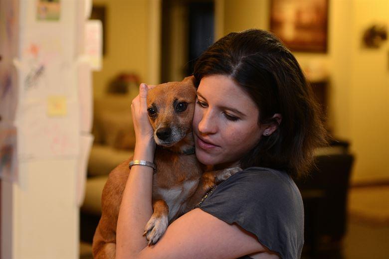 Женщина держит на руках собаку фото