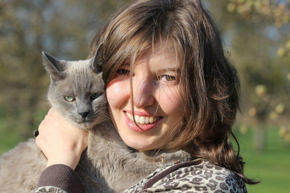 Женщина улыбается и обнимает кота фото