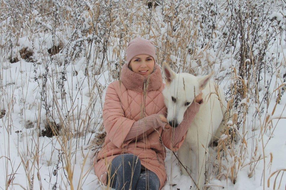 Белая швейцарская овчарка с хозяйкой на снегу фото