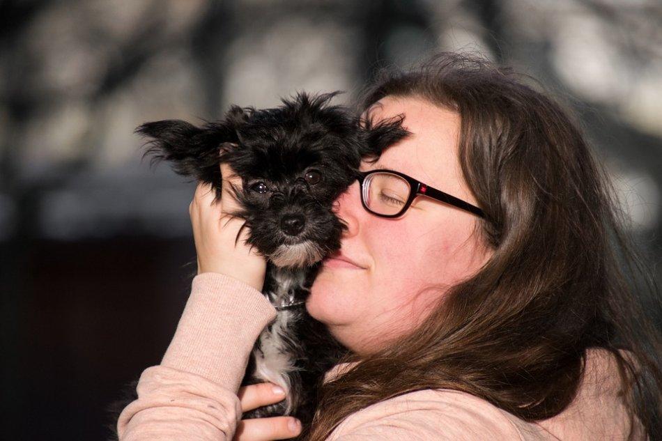 Женщина обнимает маленькую черную собачку фото