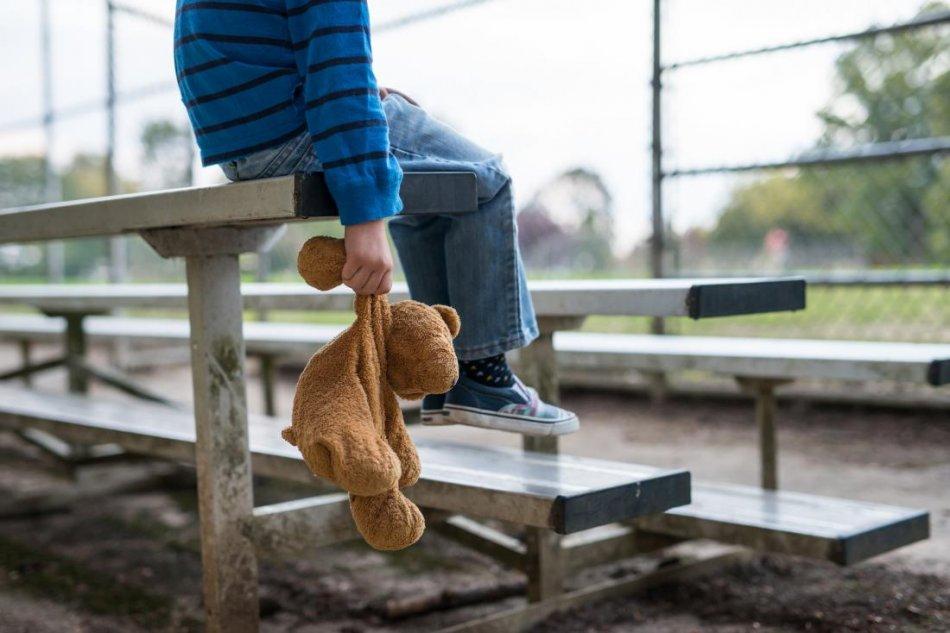 Ребенок держит за лапу плюшевого медвежонка фото